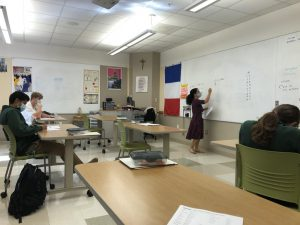 Madame Horning, who previously taught at Mount Pleasant High School, demonstrates verb conjugation to her socially-distanced French II students at Archmere.