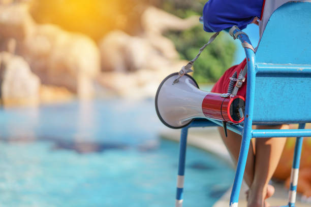 lifeguard sitting on chair with megaphone at poolside for guarding lives